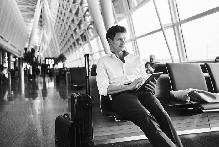 Fabian Unternaehrer Aduno Mann Flughafen Wartehalle tablet